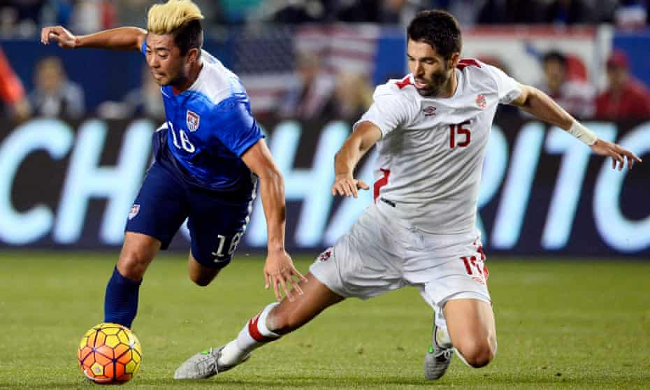 Lee Nguyen (left) tussles for the ball with Canada's Steven Vitoria