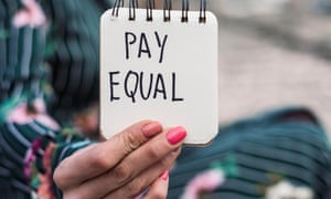 Woman holds notepad saying: pay equal