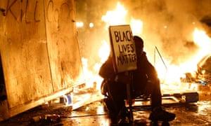 A demonstrator sits in front of a street fire in Ferguson