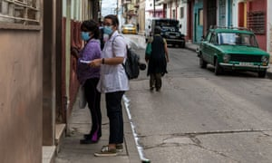 A medical student knocks on doors to investigate and early detect possible coronavirus cases in Santa Clara, Cuba, 19 Jan 2021.