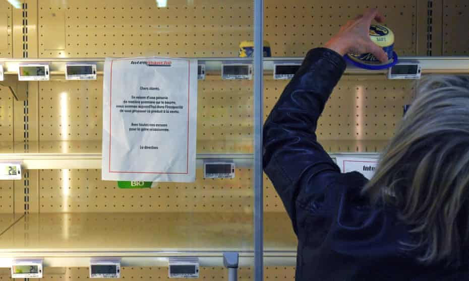 A woman grabs the last pack of butter from an empty refrigerated supermarket shelf