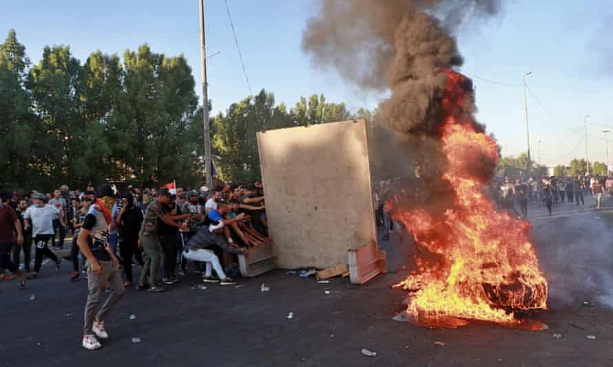 Protesters set fires and close a street in Baghdad.
