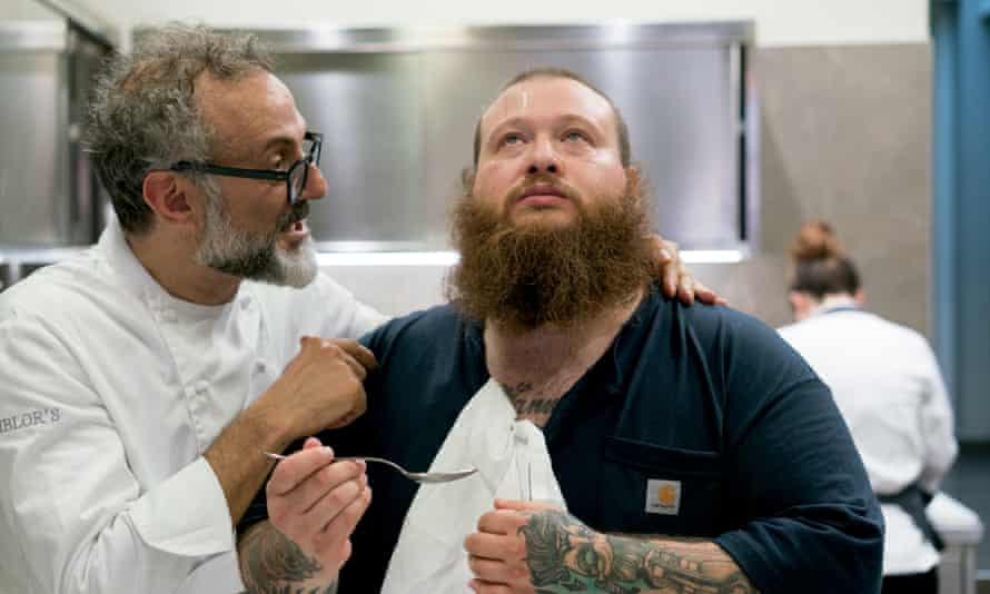 Action Bronson looking up with a spoon in his hand and Massimo Bottura looking at him with his hand on his neck