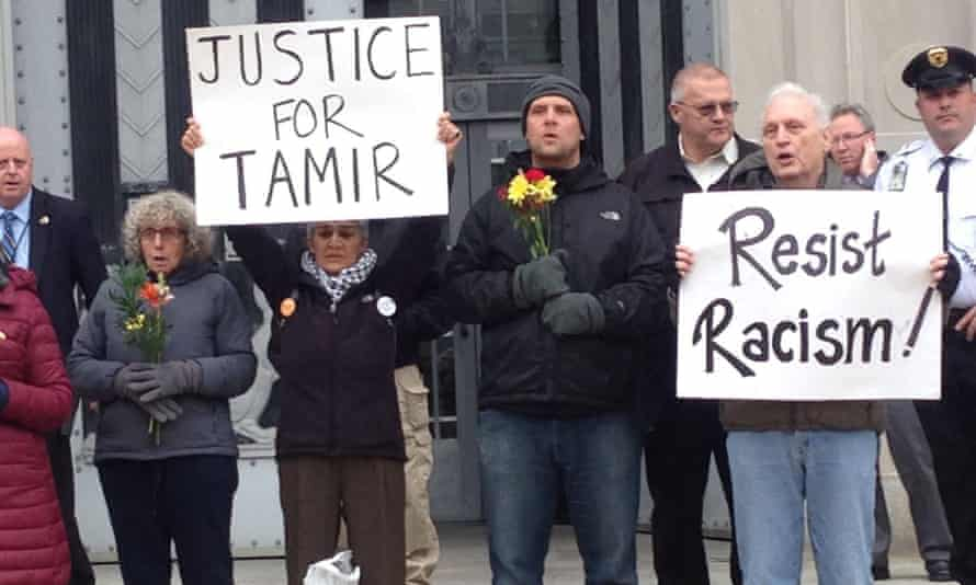 In this 2016 photo Gugino holds a sign reading 'Resist Racism' as part of a protest in Washington over the police killing of 12-year-old Tamir Rice.