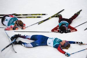 Switzerland's Nathalie von Siebenthal, Jessica Diggins of the US and Austria's Teresa Stadlober fall exhausted at the end of the women's cross-country 7.5km + 7.5km skiathlon.
