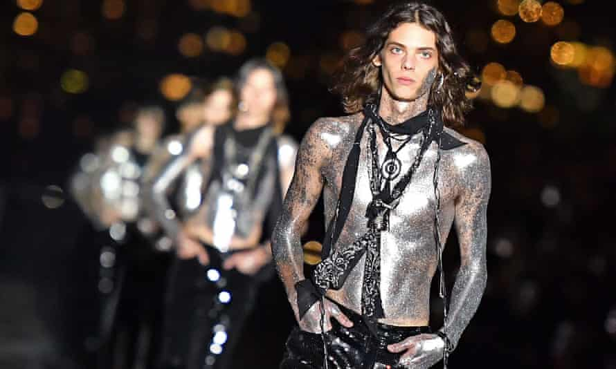 Male models sprayed silver at the Saint Laurent show