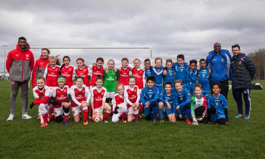The teams pose after the match. One of the girls says: 'It is not helping you to improve if you win 20-0 or 30-0. It is better to lose 1-0 against the boys.'