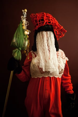 A medium shot of a mummerer, wearing a red dress and a cream veil, and holding an ornate head-high stick. House visits are now the most common form of mummering. A group of mummers will call on friends and neighbours, where they get up to hijinks, play music, dance and act the fool. It is then the hosts' job to guess the identity of each masked mummer. Once they have been correctly identified, they can remove their masks.