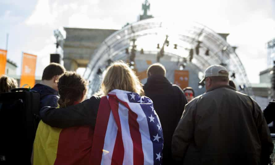 Women carrying German and US flags wait for Obama and Merkel to appear.