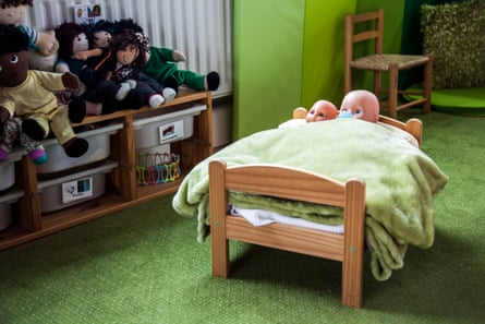 A toy bed with dolls in it, with other toys in boxes behind, at a playroom run by Triangle, an organisation that helps children give evidence