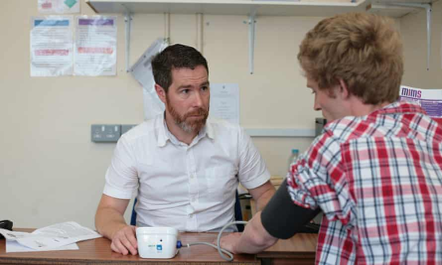 Male GP taking blood pressure of a young man