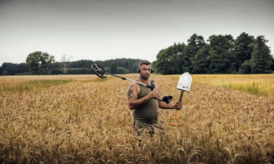 Field of dreams: Dariusz looking for treasure with a metal detector and shovel.