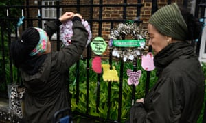 People leave messages on railings near Grenfell Tower