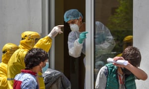 A hospital worker (C) wearing a protective face mask and outfit, speaks with two ambulance doctors wearing yellow protective suits at the Grigor Lusavorich Medical Centre in Yerevan amid the COVID-19 pandemic.
