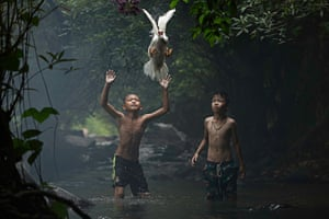 Two boys trying to catch a duck at the stream of the waterfall in Nong Khai province, Thailand