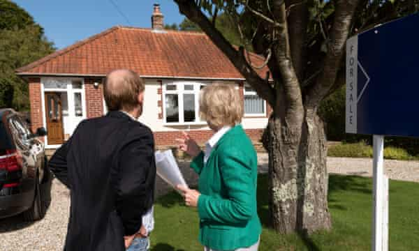 House buyers viewing a house with a for sale sign.