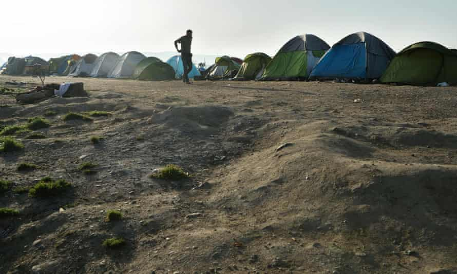 A refugee man walks in the makeshift camp at the Greek-Macedonian border