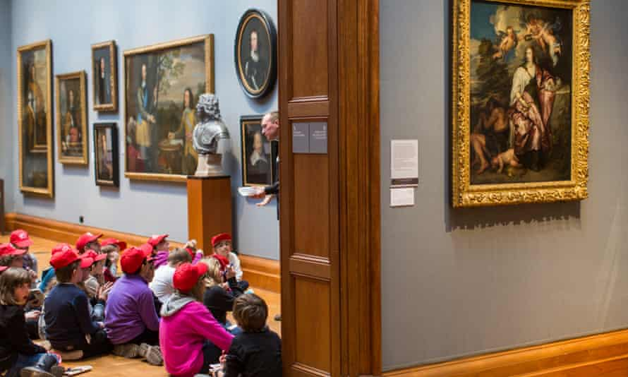 Schoolchildren, wearing red caps, sitting on the floor in the National Portrait Gallery, London