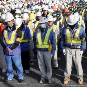 Decontamination workers observe a moment of silence to mourn victims of the March 11, 2011 earthquake and tsunami disaster before their work in Namie, Fukushima