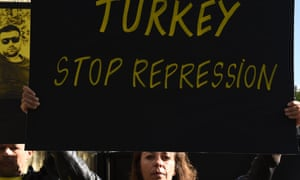 A woman holds a sign highlighting Turkey's detention of human rights activists at a protest in Paris on 20 July.