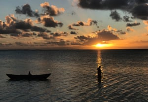 A fisherman returns home at dusk on his traditional wooden outrigger near the village of Ambo on South Tarawa.