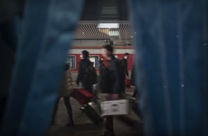 People disembark at a railway station in Shijiazhuang, Hebei province