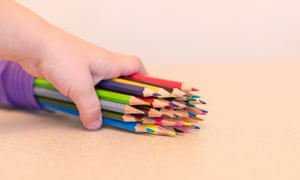A child holding some coloured pencils
