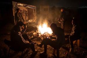 Men sit by a fire