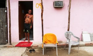 A resident stands in the doorway of his home in the mostly demolished Vila Autódromo favela community in Rio de Janeiro, Brazil
