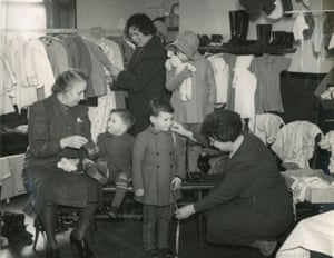 Children trying on clothes at the children's clothing exchange, Hastings, Sussex, 4 March 1944