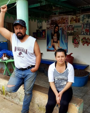 Anti-mining actvists Alex Reynoso, 37, and his wife Irma, 41, sitting in front of a montage of their daughter Tapocio, who was shot dead in 2014 when she was 17. Alex survived the attack.