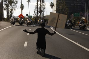 """A man kneels on the street in front of police officers while chanting """"I can't breathe"""" in Los Angeles."""