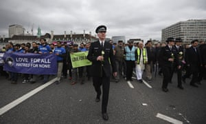 Met police Supt Jon Williams holds a white rose during the vigil on Westminster Bridge.