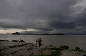 Guwahati, India - A man prepares to collect water as rain clouds loom over the Brahmaputra river in north-eastern Assam state