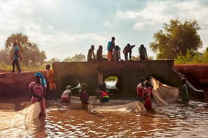 Refugees join the local community to fish at a stream formed by intense flooding in Maban, South Sudan.