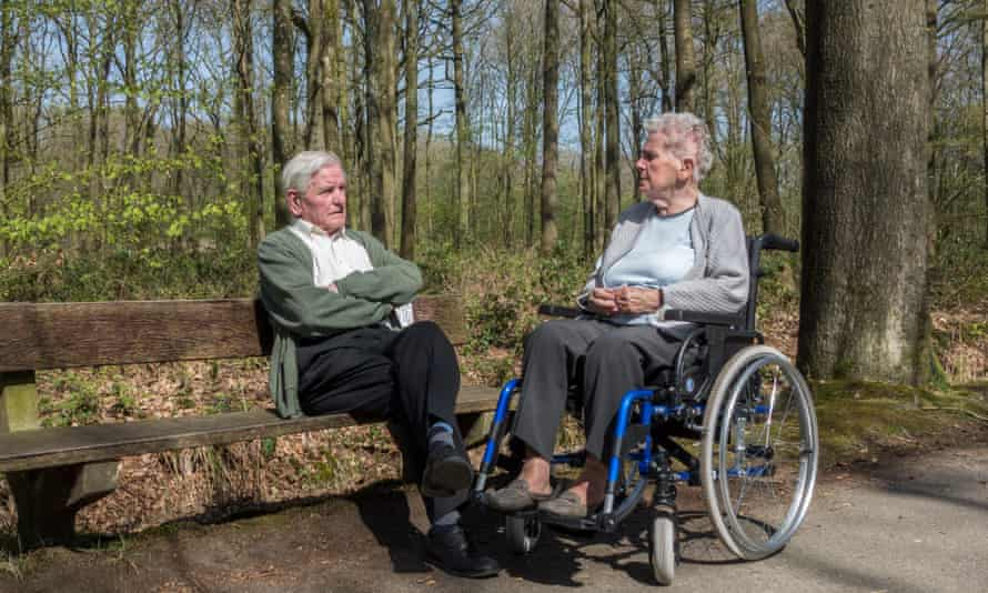 Elderly man speaks to his wife, who is in a wheelchair.