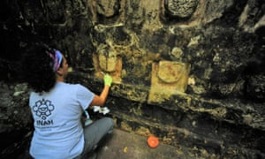 An archaeologist cleans some of the building uncovered in Kulubá