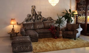 A pack of cheetahs crouch over a zebra-print sofa, where entrails snake out of a cushion