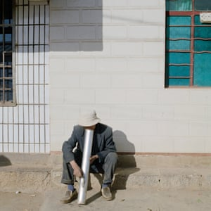 Yuxi, China. A man smoking using a water pipe