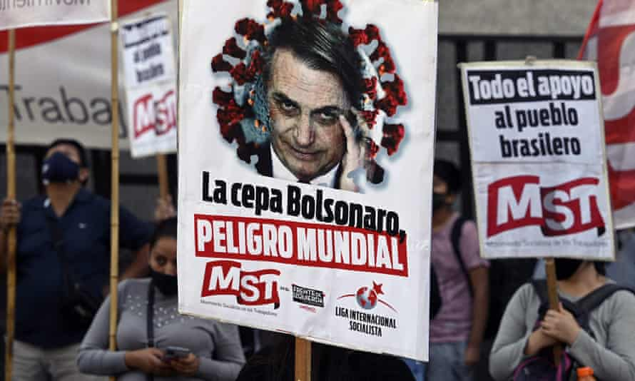 People hold banners depicting Brazil's President Jair Bolsonado reading 'The Bolsonaro strain, world danger' during a protest of members of leftist parties outside the Brazilian embassy in Buenos Aires on Wednesday.