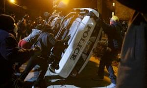Protesters flip over a Ferguson police car