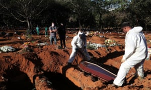 Gravediggers wearing protective suits bury the coffin of Izolina de Sousa, 85, who died from the coronavirus disease in Sao Paulo, Brazil