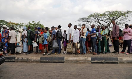 People in Lagos queue at a bus stop