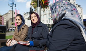 Three women in headscarves on park bench