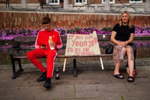 People sit on a bench next to a banner in Bristol, UK