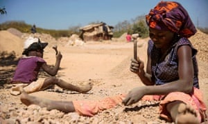 A woman and child break rocks extracted from a cobalt mine in Lubumbashi, DRC