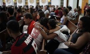 两名穿着弗拉门戈足球包的年轻女子为了纪念火灾的受害者而拥抱。