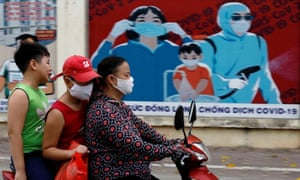 Residents ride past a banner on coronavirus protection in Hanoi