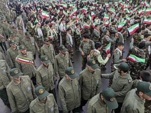 School pupils wave national flags as the Revolutionary Guards arrive in Azadi Square