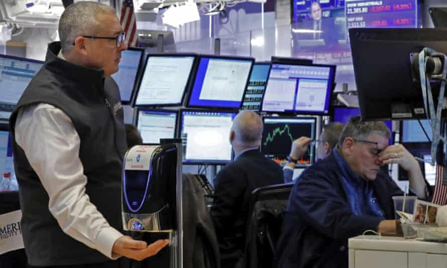 A trader uses a hand sanitiser dispenser on the floor of the New York Stock Exchange